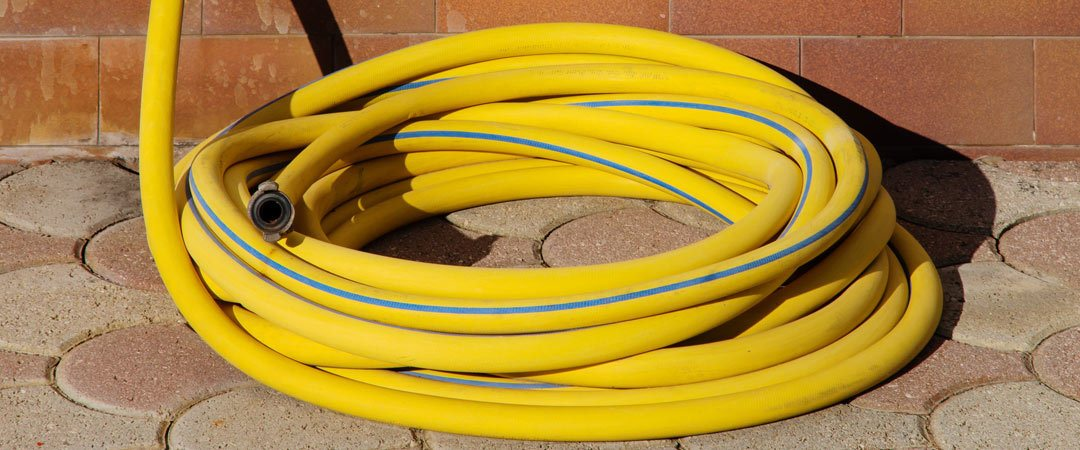 Yellow hose on brick patio