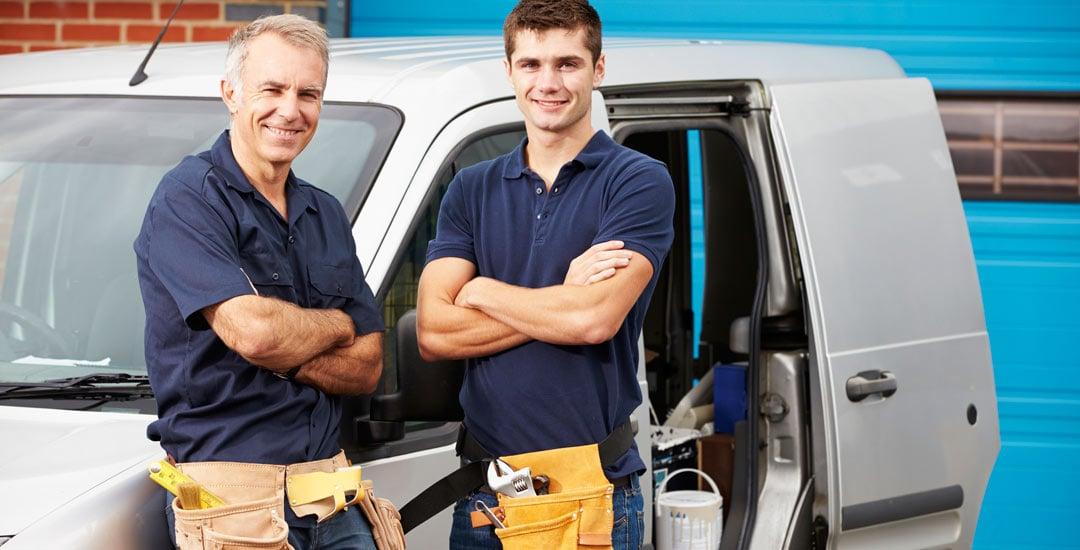 Two plumbers standing in front of their van