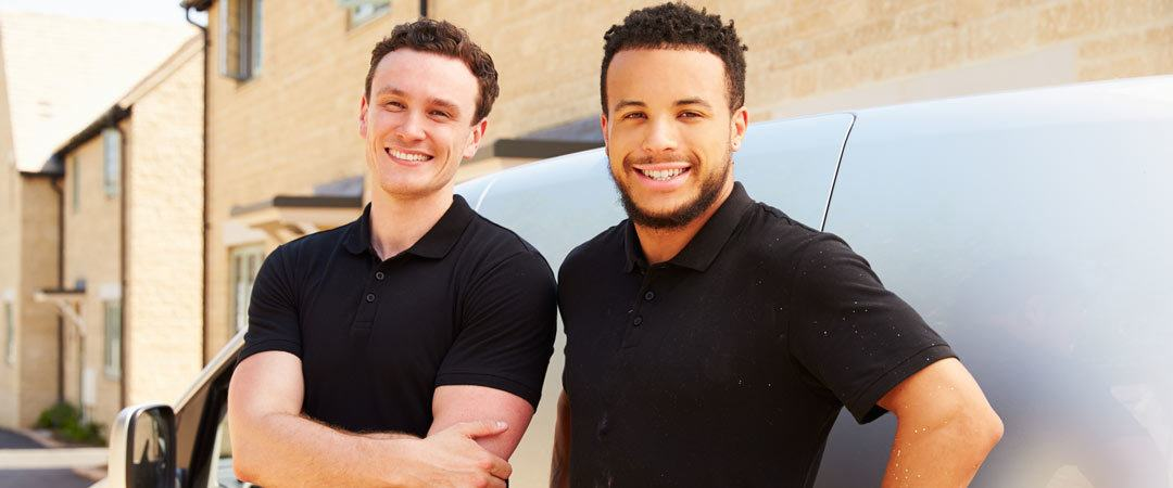 Two plumbers leaning against a white van