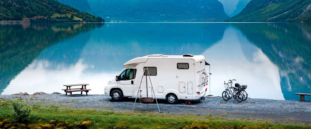 RV parked in front of a lake