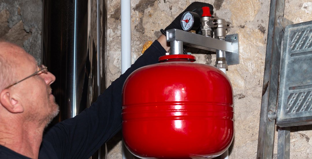 Man installing a water heater expansion tank